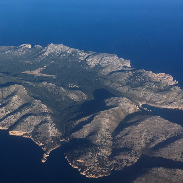 Helikopterperspektiv på en grönskande ö.