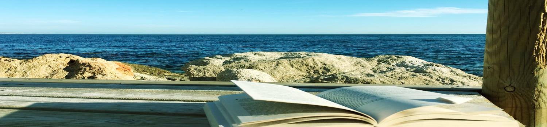 En öppen bok liggandes på en brygga med klippor och mörkblått hav i bakgrunden.